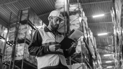 Overseer Wearing Hard Hat with Clipboard Fills in Forms in a War